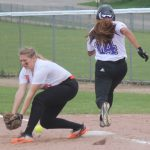 Belding's Jo VanderRoer, left, drops a ball that allowed Greenville's Addie Chesebro, right, safe at first during the first game of the two teams' doubleheader Friday.
